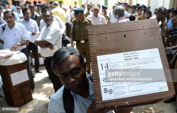 A Sri Lankan election worker carries a ballot box before boarding on a bus as he prepares to go to a polling centre in Colombo February 9 2018 Sri...