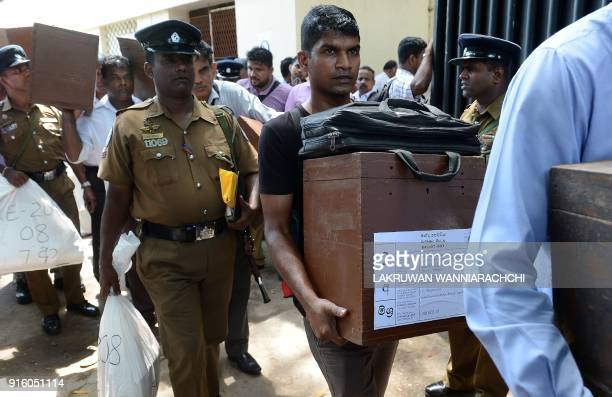 Sri Lankan election workers and police officers carry ballot boxes before boarding on buses as they prepare to go to their polling centres in Colombo...