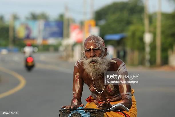 Sri Lankan ethnic Hindu priest rides bicycle in street on October 25 2015 in Jaffna Sri Lanka Sri Lankan Prime Minister Ranil Wickremesinghe seeks...