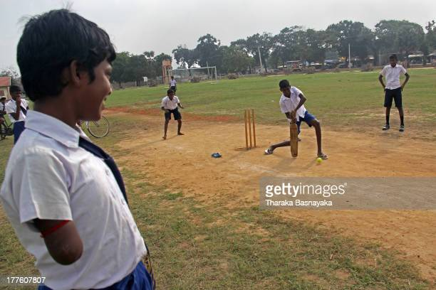 Sri Lankan Ethnic Tamil child, disabled, during the war between the 'LTTE' and Sri Lankan army , looks on at his friends playing cricket at a play...