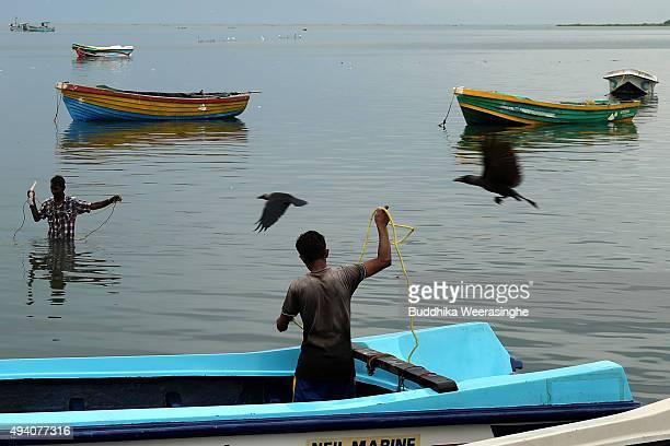 Sri Lankan ethnic Tamil fishermen prepare their fishing nets at Gurunagar fishing port on October 24 2015 in Jaffna Sri Lanka Sri Lankan Prime...