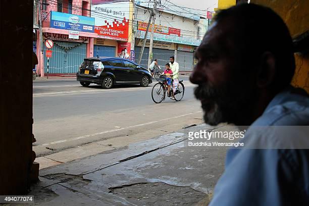 Sri Lankan ethnic Tamil man rides bycycle with his son in a street on October 24 2015 in Jaffna Sri Lanka Sri Lankan Prime Minister Ranil...
