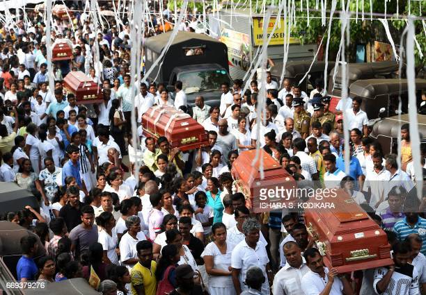 Sri Lankan families carry the coffins of victims who died following the collapse of a garbage dump in Colombo on April 17 2017 Sri Lanka has moved...