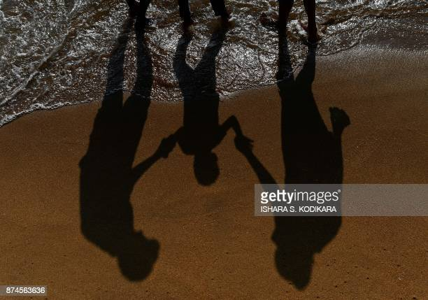 Sri Lankan family stand at the water's edge at Galle Face Beach in the heart of the Sri Lankan capital Colombo on November 15 2017 / AFP PHOTO /...
