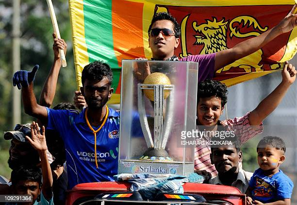Sri Lankan fans parade with a replica of the 2011 cricket World Cup on a street in Colombo on February 13 2011 Sri Lanka champions in 1996 and...