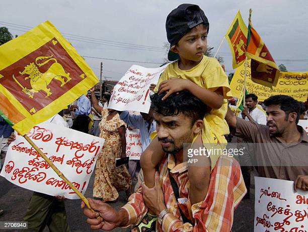 Sri Lankan father waves a flag as he carries his four year old son on his shoulders whilst taking part in an anti Wickremesinghe pro Kumaratunga...