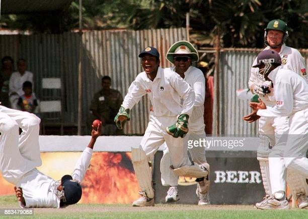 Sri Lankan fielder Russel Arnold holds the ball after a catch to dissmis South African batsman Darryl Cullinan as wicket keeper Kumar Sangakkara...