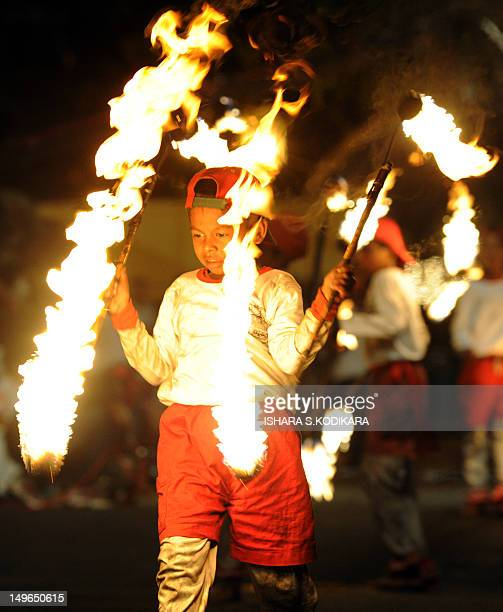 Sri Lankan fire dancers perform outside the historic Buddhist Temple of the Tooth, as they take part in a procession during the Esala Perahera...