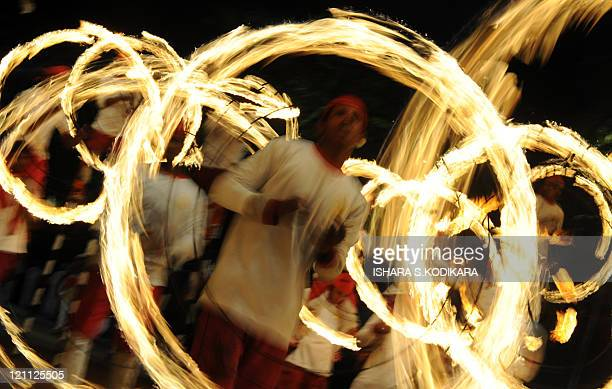 Sri Lankan firedancers perform outside the Buddhist Temple of the Tooth, as they take part in a procession during the Esala Perahera festival in...