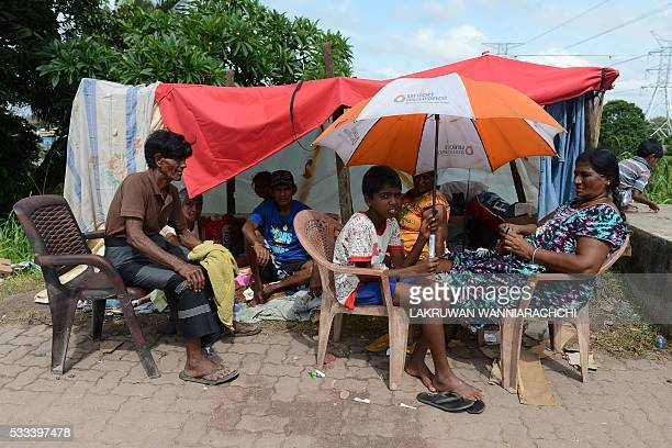 Sri Lankan flood victims gather at a roadside temporary shelter at Kelaniya bridge on the outskirts of Colombo on May 22 2016 Sri Lankan soldiers...