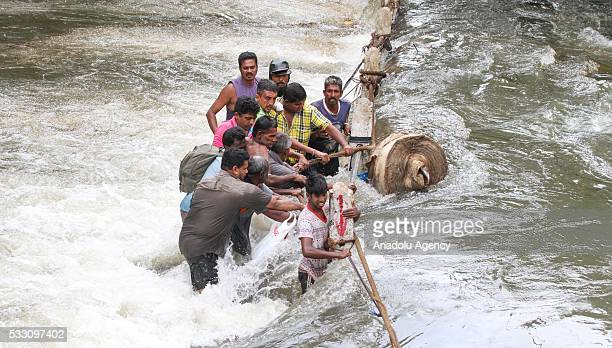 Sri Lankan flood victims struggle to cross floodwaters in Kelaniya outskirts of Colombo Sri Lanka on May 20 2016