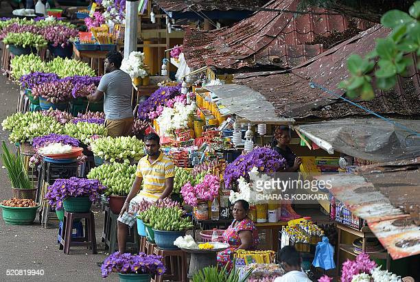 Sri Lankan flower sellers arrange lotus flowers outside a Kelaniya Buddhist Temple in celebration of the traditional Sinhala and Tamil New Year in...
