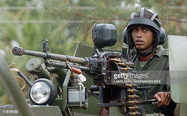 Sri Lankan government special forces commando mans a medium machine gun mounted on an armoured vehicle in the town of Sampur 07 September 2006 after...
