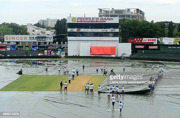 Sri Lankan groundstaff remove the covers during the opening day of their third and final Test cricket match between Sri Lanka and India at the...