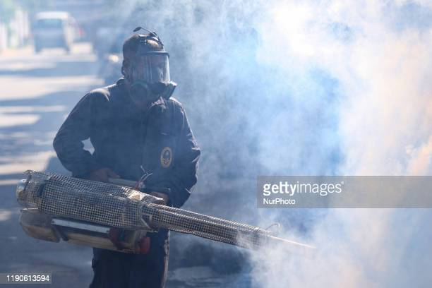 A Sri Lankan health worker walks amid the smoke from an antimosquito fumigation machine in Colombo Sri Lanka Friday 27 December 2019 Following over...