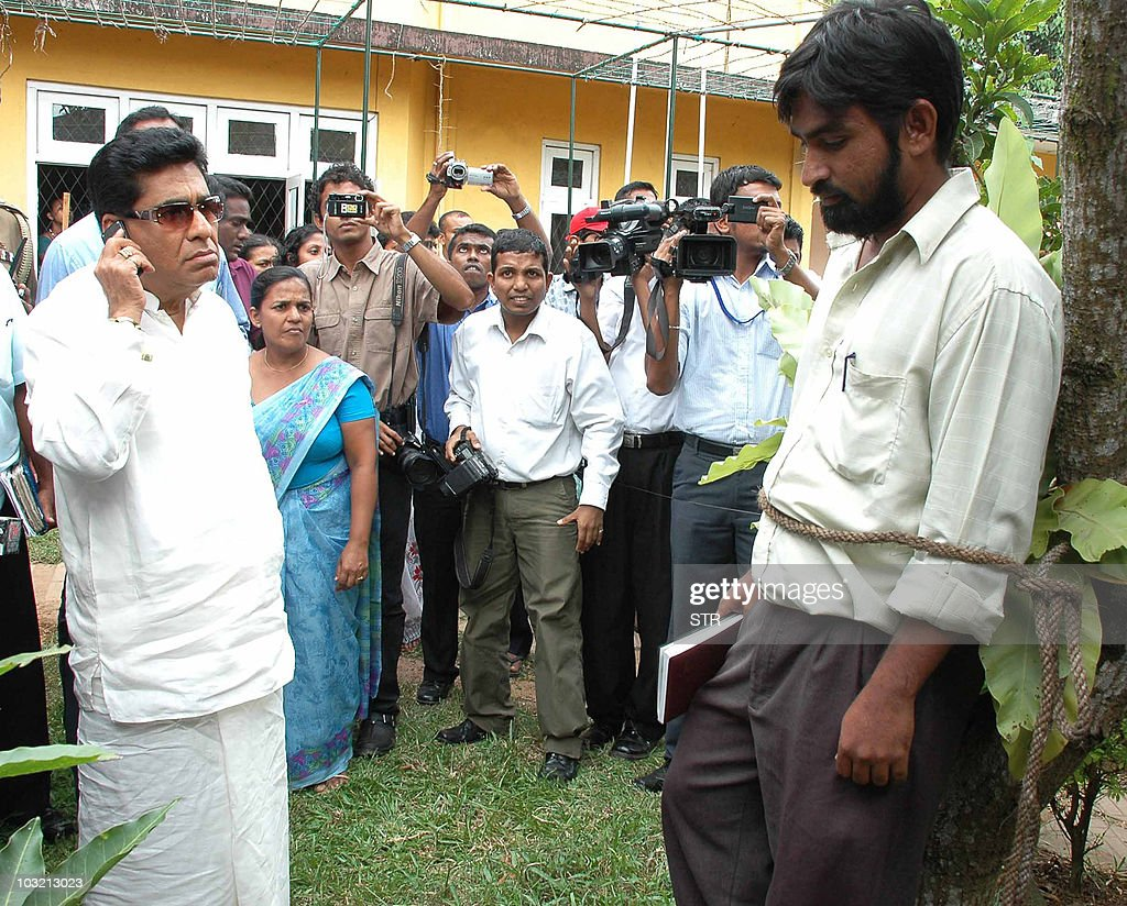 Sri Lankan Highways Minister Mervyn Silva (L) inspects an unidentified local municipal official who was tied to a tree at the local authority office in the Colombo suburb of Kelaniya on August 3, 2010 as punishment for not controlling the spread of dengue. The mosquito-spread disease has claimed 171 lives and infected nearly 25,000 people so far this year, according to Sri Lankan health records.
