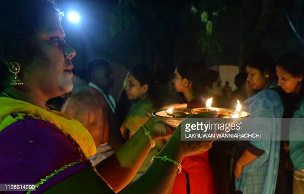 A Sri Lankan Hindu devotee offers prayers while holding an oil lamp during the Maha Shivaratri festival at a Hindu temple in Colombo on March 4 2019...