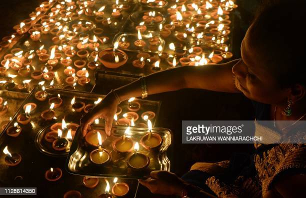 Sri Lankan Hindu devotee offers prayers while holding an oil lamp during the Maha Shivaratri festival at a Hindu temple in Colombo on March 4, 2019....