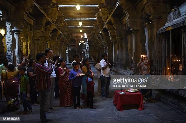 Sri Lankan Hindu devotees offer prayers at a Hindu temple in Colombo on January 14 2017 Hindus in Sri Lanka are celebrating the Thai Pongal festival...