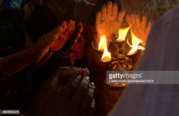 Sri Lankan Hindu devotees receive blessings from a priest at a Hindu Temple in Colombo on January 14 2014 Hindus in Sri Lanka are celebrating the...