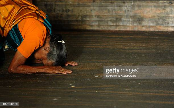 A Sri Lankan Hindu woman offers prayers at a Hindu Temple in Colombo on January 15 2012 Hindus in Sri Lanka are celebrating the Thai Pongal festival...