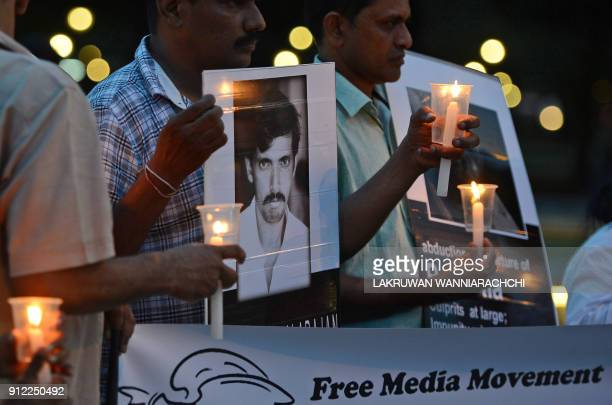Sri Lankan journalists and activists hold candles during a vigil for murdered colleagues in Colombo on January 30 2018 Sri Lankan journalists and...