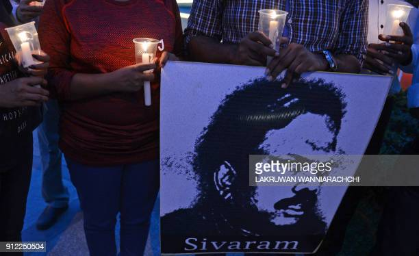 TOPSHOT Sri Lankan journalists and activists hold candles during a vigil for murdered colleagues in Colombo on January 30 2018 Sri Lankan journalists...