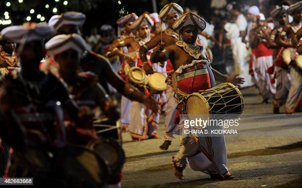 Sri Lankan Kandyan dancers perform in front of the Gangarama Temple as they take part in a procession during the Navam Perahera festival in Colombo...