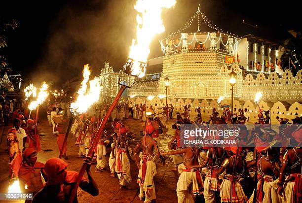 Sri Lankan Kandyan dancers perform in front of the historic Buddhist Temple of the Tooth, as they take part in a procession during the Esala Perahera...