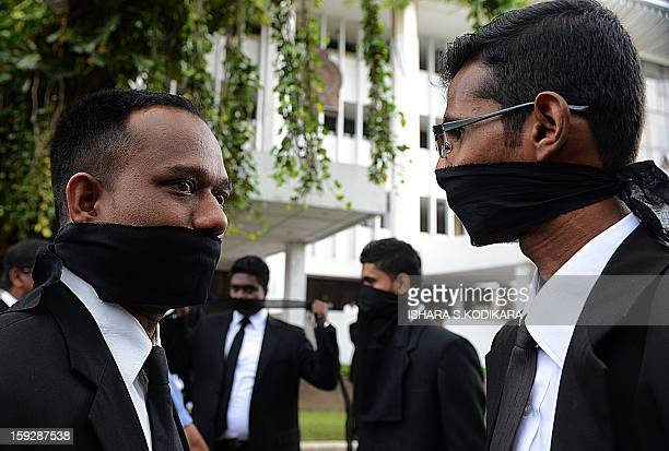 Sri Lankan lawyers their mouths gagged with black cloth protest against the government's move to impeach Chief Justice Shirani Bandaranayake in the...