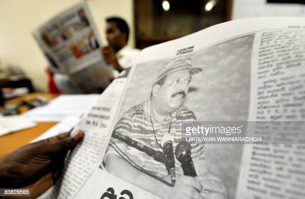 A Sri Lankan man browses through a newspaper bearing a picture of leader of the Liberation Tigers of Tamil Eelam Velupillai Prabhakaran in Colombo on...