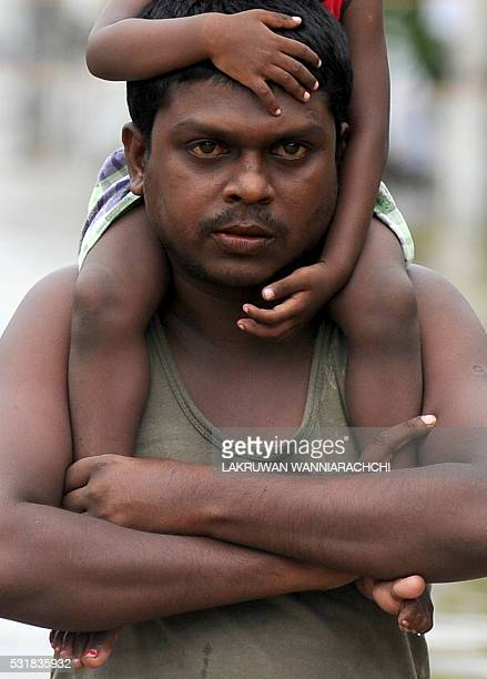 A Sri Lankan man carries a child on his shoulders as he makes his way through floodwaters in the suburb of Kaduwela in capital Colombo on May 17 2016...