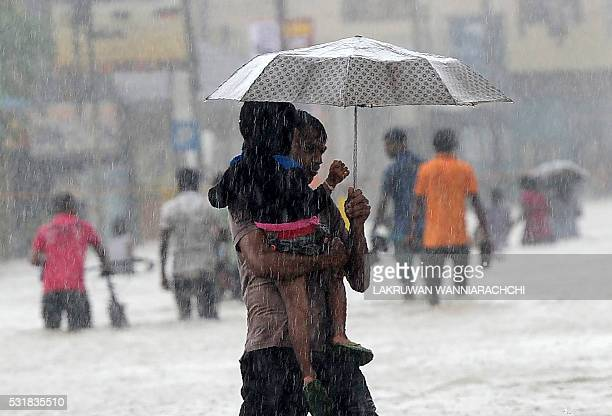 Sri Lankan man carries a child through floodwaters in the suburb of Kaduwela in capital Colombo on May 17 2016 Emergency workers in Sri Lanka on May...