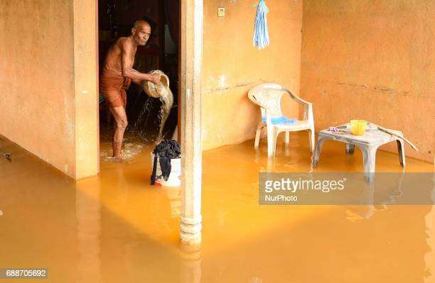 A Sri Lankan man cleans his house inundated by flood water at Kaduwela 20kms away from capital city Colombo Sri Lanka Friday 26th May 2017 More than...