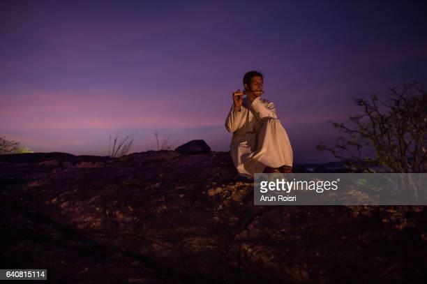 Sri Lankan man play traditional music after sunset in wilderness location for VIP tourist in Kandalama,Sri Lanka