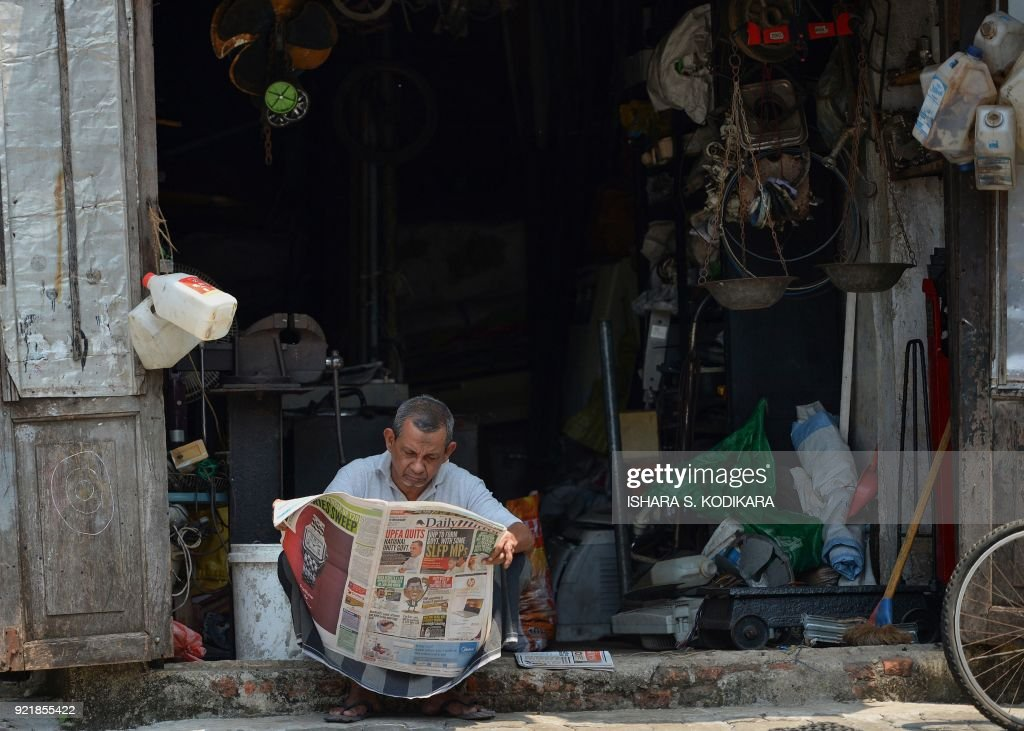 A Sri Lankan man reads a newspaper outside of a shop in Colombo on February 21, 2018. /