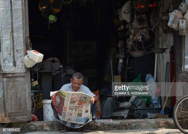 A Sri Lankan man reads a newspaper outside of a shop in Colombo on February 21 2018 / AFP PHOTO / ISHARA S KODIKARA
