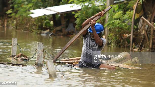 A Sri Lankan man rows a makeshift raft on a flooded road in Godagama Matara Sri Lanka Tuesday 30 May 2017