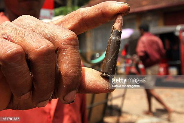 Sri Lankan man shows a mettal bullet, he collected from the ground in the village of Weliweriya on the outskirts of Colombo on August 02, 2013. Sri...