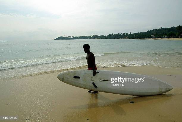 Sri Lankan man takes his surfboard out to sea in the southwestern coastal town of Galle 04 January 2005 Heavy rains slowed relief operations in Sri...
