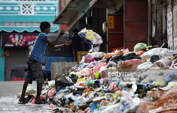 A Sri Lankan man throws garbage onto a rubbish pile on a street in Colombo on April 18 2017 Hundreds of tonnes of rotting garbage piled up in Sri...