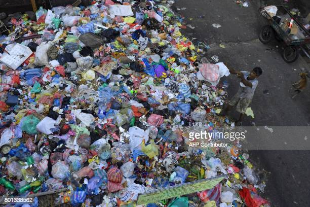 A Sri Lankan man throws trash onto garbage piled on a street in Colombo on June 26 2017 Sri Lanka has suffered a record 200 deaths from dengue fever...