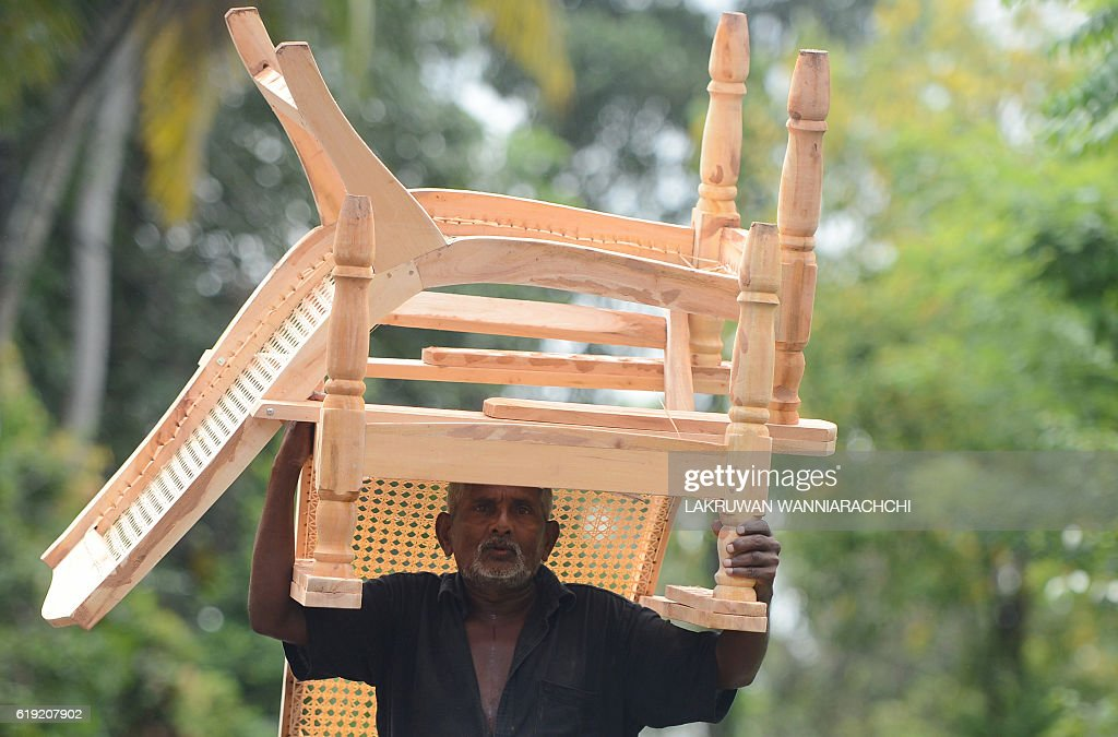 A Sri Lankan man transports furniture for sale in Colombo on October 30, 2016. Sri Lanka new government secured a 1.5 billion dollar bailout from the International Monetary Fund in June after facing a balance of payments crisis and has also negotiated cheaper funding from international lenders. / AFP / LAKRUWAN
