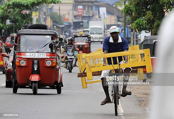 A Sri Lankan man transports furniture for sale on his bicycle in Colombo on October 20 2013 The IMF expects growth for the current calendar year to...
