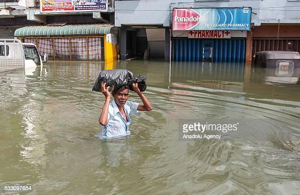 Sri Lankan man tries to cross a flooded street in Wellampitiya outskirts of Colombo Sri Lanka on May 20 2016