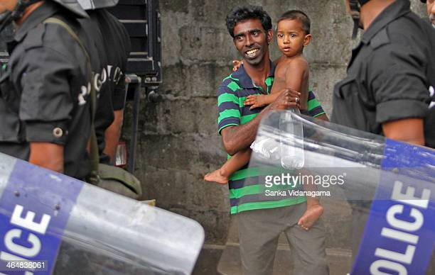 Sri Lankan man tries to hide behind anti-riot squads with his child during a clash between two religious factions in the capital Colombo on August 11...