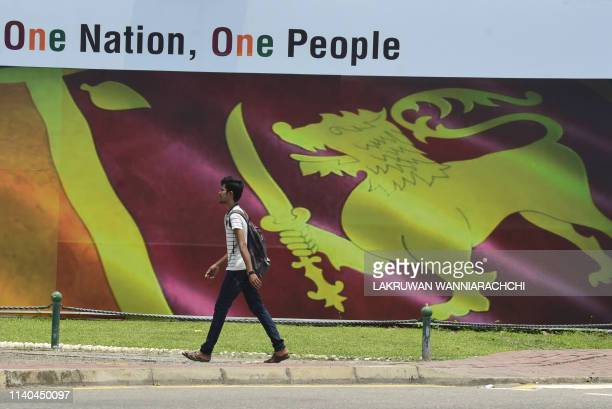A Sri Lankan man walk past a large image of Sri Lanka's national flag in Colombo on May 1 2019