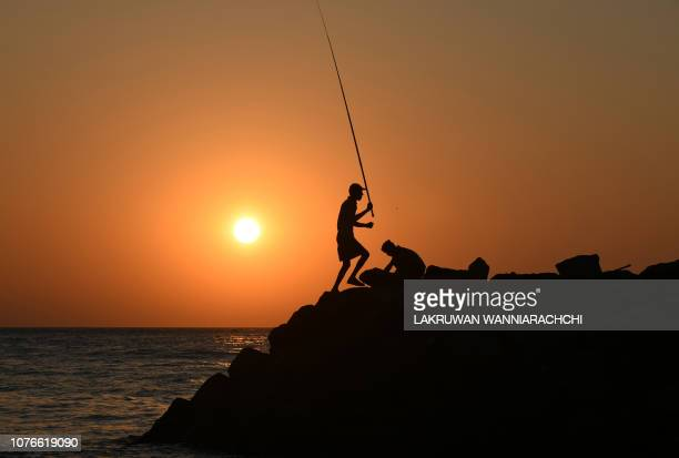 Sri Lankan men fish during sunset on a beach in Colombo on January 3 2019