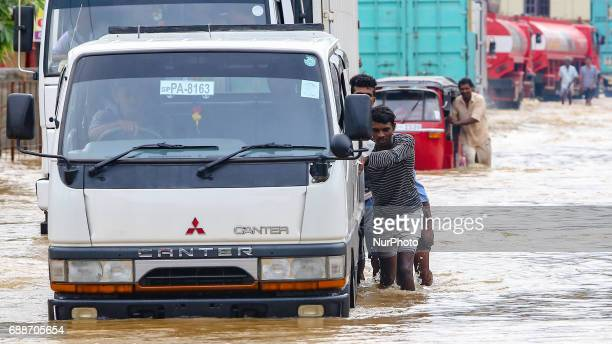 Sri Lankan men push their vehicles across a road against the inundated water caused by floods at Kaduwela 20kms away from capital city Colombo Sri...