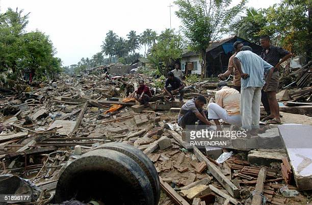 Sri Lankan men sort through debris of their destroyed homes after a massive tidal wave struck the southern district of Galle 27 December 2004 Sri...